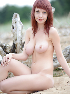 Redhead cutie with perfectly round big tits unveils her body on a sandy beach
