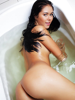 Lovely raven-haired stunner Macy B unveils her shaved muff in the bathroom