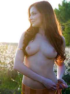 Gorgeous Russian redhead prances nude among the pretty flowering trees