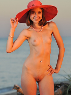 Teenager outdoors on the sandy shore of the lake with her little tits exposed