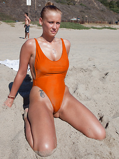 Big natural tits and a curvy ass look hot in an orange swimsuit on the beach
