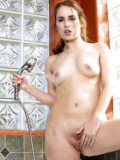 Seductive redhead Kiki Vidis drops her bathrobe and masturbates in the bathtub