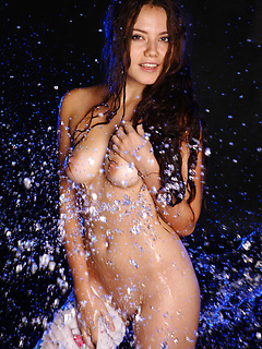 Water splashes brunette beauty Norma as she peels off her clothes for erotic pics