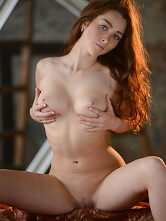 Elegance oozes from the redhead in a gorgeous dress as she indulges in a sexy striptease