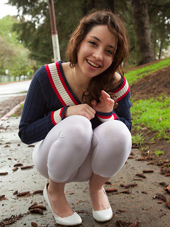 Curly hair teen cutie plays outdoors in a sweater and sheer tights