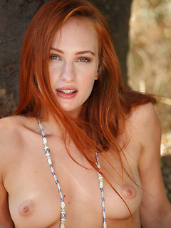 Sensual redhead looker Sally A exposes her beaver and small tits under a tree