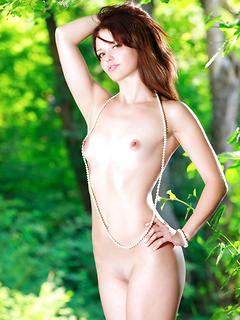 Elegant model in a white wedding dress strips fully nude in the green of nature