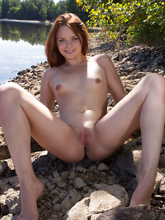 Redhead in a bra and panty set plays on a rocky beach and strips to pose naked outdoors