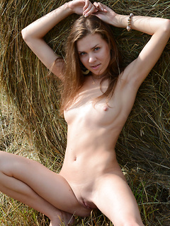 Farm girl strips in the middle of a field and poses naked next to a bale of hay