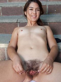 Hairy cutie with a wonderful bush growing between her legs shows it off